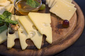 Wooden plate with cheese — Stock Photo