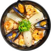 Suppe mit Meeresfrüchten, Calamari, Garnelen, Muscheln in einem schwarzen Teller auf weißem Hintergrund — Stockfoto