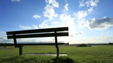 Time lapse of clouds rolling above a bench on a sunny day — Stock Video