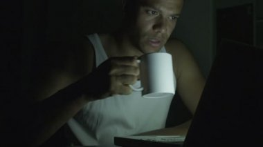 Man on his laptop late at night drinking from a cup — Stock Video