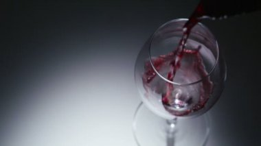 Red wine poured  into a glass in slow motion — Stock Video