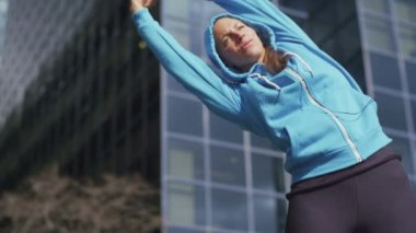 Woman in hoodie stretching — Stock Video