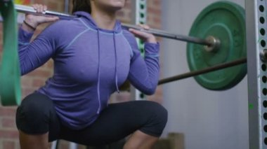 Woman squats with a barbell in gym — Stock Video
