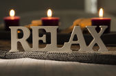 Text of the words relax with burning candles — Stock Photo