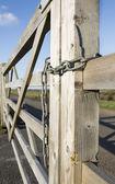 Locked chain around a wooden gate — Stock Photo