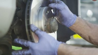 Mechanics hands installing a brake disc in slow motion — Vídeo stock