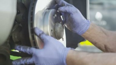 Mechanics hands installing a brake disc in slow motion — Vídeo de Stock