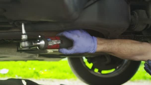 Manos de un mecánico pernos desenroscado bajo un automóvil en cámara lenta — Vídeo de stock