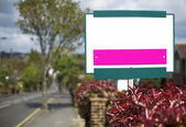 Blank placard sign outside a house on a road — Stock Photo