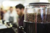 Foreground shallow depth of field of roasted coffee beans in a grinder with blurred activity in the background — Stock Photo