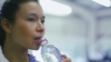Attractive woman drinks bottled water in the gym — Stock Video