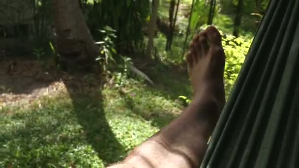 Relajante pies de un hombre en una hamaca en un ambiente tropical — Vídeo de stock