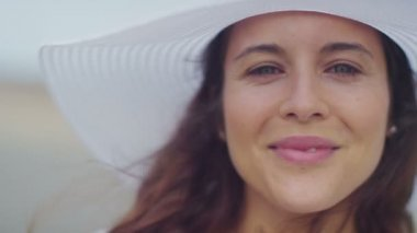 Attractive woman in a hat smiling to camera in slow motion — Vídeo de Stock