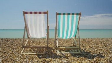Two empty deck chairs on a beach on a bright sunny day looking out to sea — Stock Video