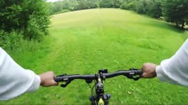 Biker rushes down a hill in a meadow — Stock Video