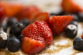 Close up of strawberries and blueberries on a pancake covered in icing sugar and maple syrup — Stock Photo