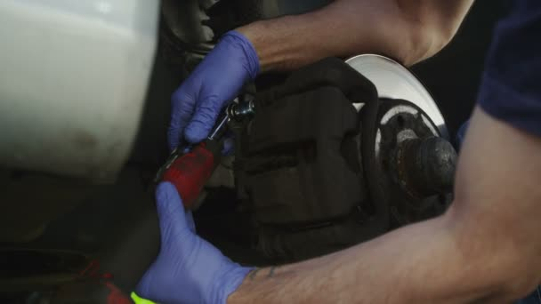 Car mechanic removing parts from a brake disc in slow motion — Vídeo de stock