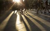 Crowds walking in a busy city district as the sun flares between them in the late afternoon creating long shadows on the ground — Stock Photo