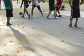 Unrecognized basketball players engaging in a game on an outdoor court in a park with leaves scattered about, shallow focus. — Stock Photo