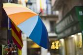 Colorful umbrella hanging along a narrow alley of shops — Stock Photo