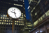 LONDON, UK - AUGUST 3, 2015 - Canary Wharf clock in the evening as office lights remain on in the background. Central finance district in London — Stock Photo