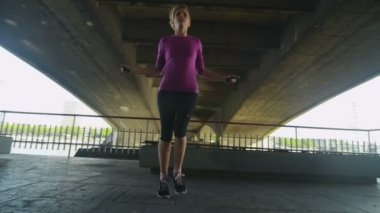 Female athlete skipping under a bridge — Stock Video