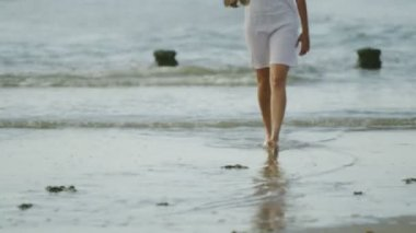 Woman walks along the beach shore — Stock Video