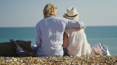 Couple sitting on the beach hug and kiss — Stock Video