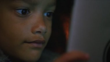 Girl watches something on a digital tablet — Vídeo stock