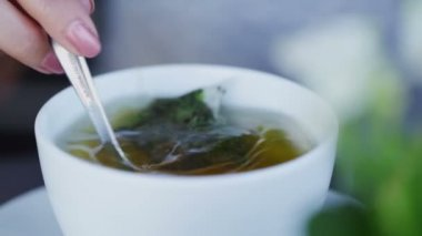 Woman stirring a herbal teabag in a cup on a cafe table — Stock Video