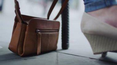 Woman's handbag on the floor as pedestrians walk — Stockvideo