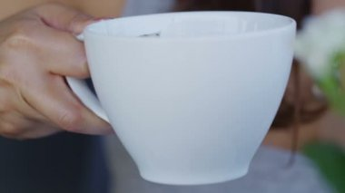 Woman gently sips her hot drink — Stock Video