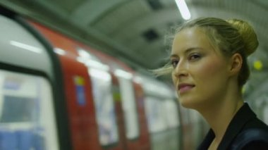 Businesswoman watches a train go past at a subway station — Vídeo stock