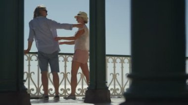 Couple embracing and enjoying the view from a balcony — Stock Video