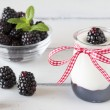 Jar with greek yogurt, blackberry jam, a red ribbon. A bowl off blackberries  and peppermint. All in a white wooden table — Stok fotoğraf #64247161