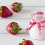 Strawberry yogurt in glass jar with a red ribbon — Stock Photo #64247949