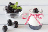 Jar with greek yogurt, blackberry jam, a red ribbon. A bowl off blackberries  and peppermint. All in a white wooden table — Fotografia Stock