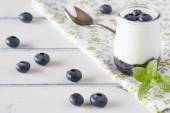 Jar with greek yogurt, blueberries jam and peppermint in a white wooden table — Stock Photo