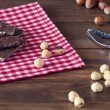 Hazelnut chocolat and hazelnuts on a red checkered napkin and a nutcracker on a wooden table — Stock Photo #64250883