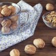 Walnuts in shells in a board with a napkin, a cup and shelled walnuts in a bowl — Stock Photo #64251037
