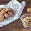 Walnuts in shells in a board with a napkin, a cup and shelled walnuts in a bowl — Stock Photo #64251051
