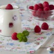 Delicious breakfast with yogurt and raspberries, a napkin and a spoon on a white wooden table — Stock Photo #64253191