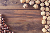 Walnuts and hazelnuts in shells on a board — Stock Photo