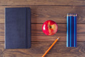 An apple, a black notebook and several pencils on a wooden table — Stock Photo