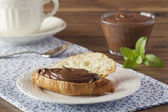 Delicious breakfast of croissant with chocolate cream on a blue napkin. A cup, a bowl, mint and a teaspoon. — Stock Photo