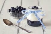 Jar with greek yogurt, blueberries jam in a white wooden table — Foto de Stock
