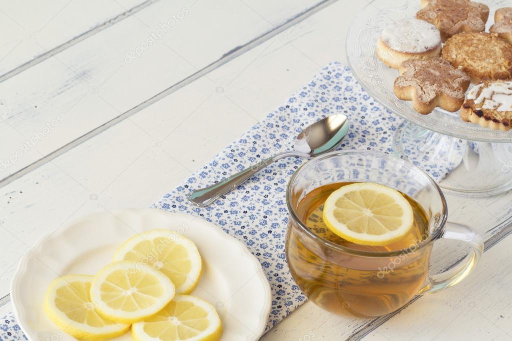 케이크 스탠드에 여러 맛 있는 독일 쿠키. 차 컵, 숟가락, 레몬의 ...