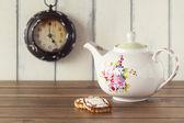 一个茶壶,两个德国饼干和一个时钟在背景中。一张白色背景的小木桌。5 上午。下午茶时间。复古风格. — 图库照片