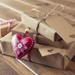 Some paper parcels wrapped tied with tags. A red heart and some christmas gift boxes wrapped with paper kraft and tied with red & white baker's twine on a wooden table. Vintage Style. — Stock Photo #64275613