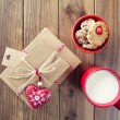 Some paper parcels wrapped tied with tags. A bowl with cookies, a milk mug for Santa, a red heart and some christmas gift boxes tied with red & white baker's twine on a wooden table. Vintage Style. — Stock Photo #64275965